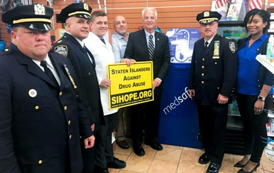 """DA Michael McMahon standing with NYPD holding The """"Staten Islanders Against Drug Abuse"""" SIHOPE.org Lawn Sign"""