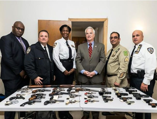 """DA McMahon, together with the NYPD, standing in front of a table with the """"gun buybacks"""